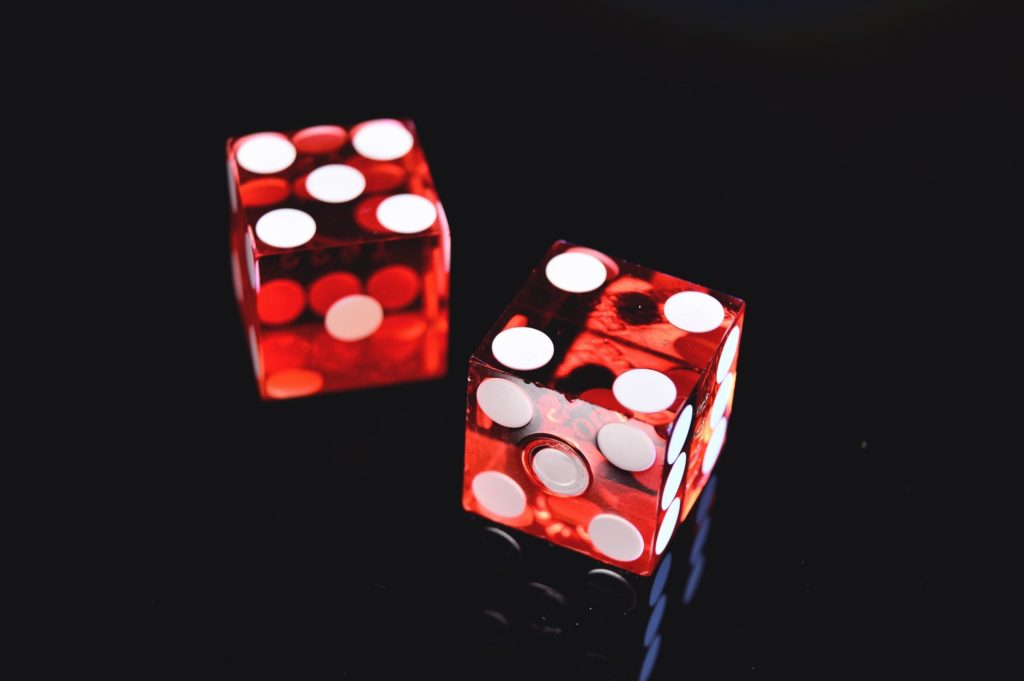 Two red dice on a black surface