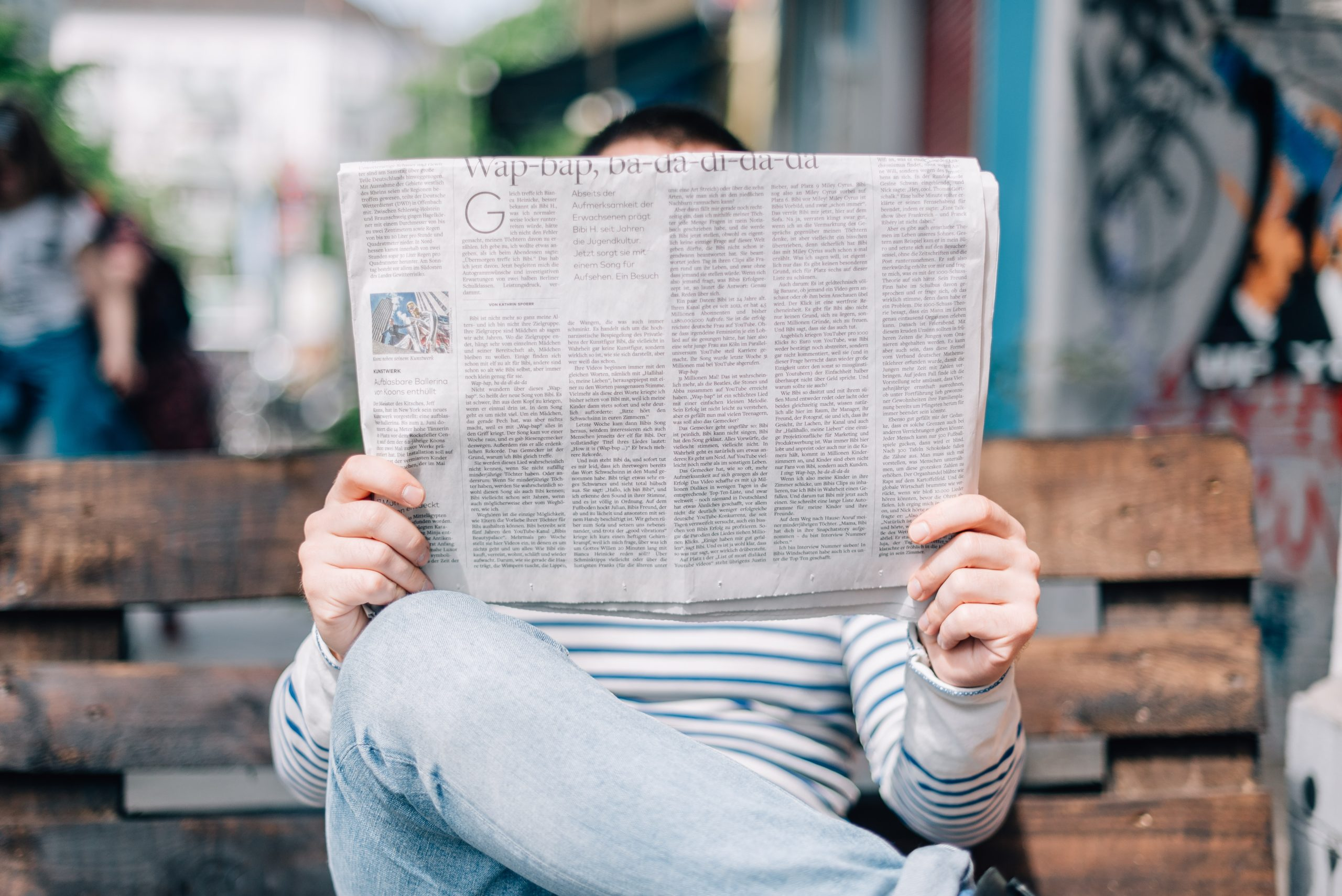 Person sitting down reading a newspaper
